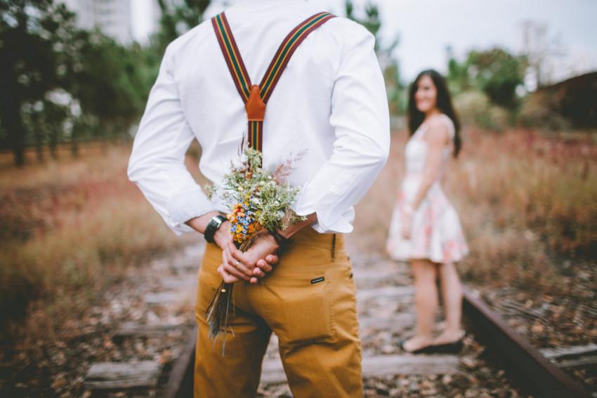 Noivo com ramo de flores atrás das costas